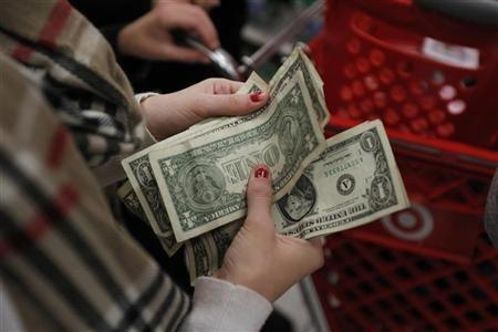 A customer counts her money while waiting in line to check out at a Target store on the shopping day dubbed ''Black Friday'' in Torrington, Connecticut