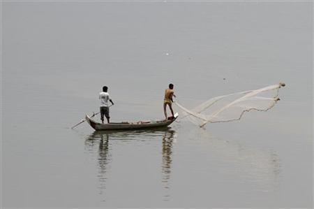 Cambodian fishermen cast their net into the Mekong River outside Phnom Penh April 19, 2011.