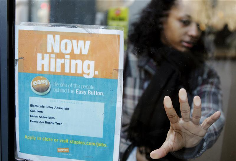 """A woman opens a glass door with a """"Now Hiring"""" sign on it as she enters a Staples store in New York"""