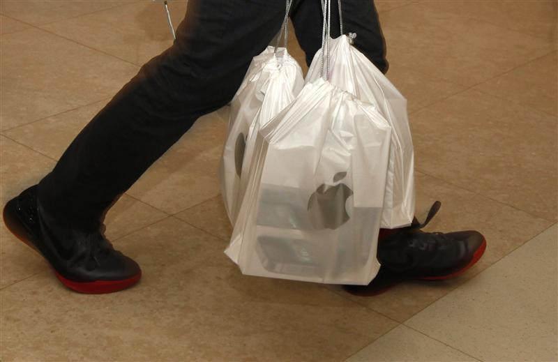 A man carries packs of Apple iPhone 4S, with each pack containing five sets, outside an Apple store in Hong Kong