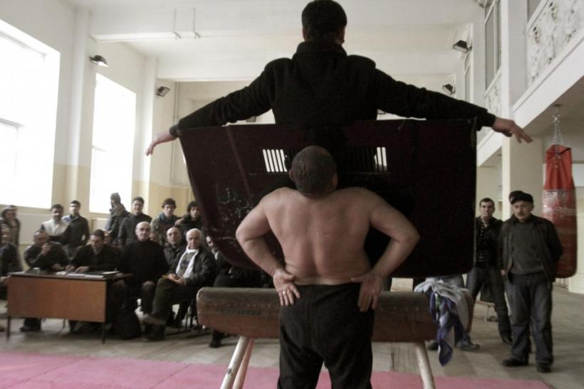 Etibar Elchyev (front) magnetizes a car hood to his body, with a man sitting on it, in a demonstration of his magnetic ability during an attempt to break the Guinness World Record for