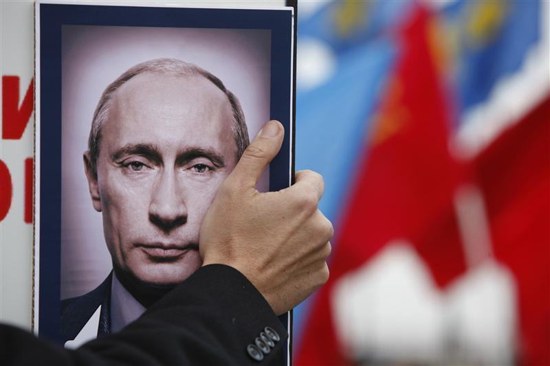 A man holds a portrait of Russia's PM Putin during a rally to protest against violations at the parliamentary elections in Stavropol