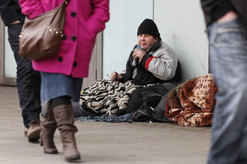 A homeless man sits on the pavement in central London