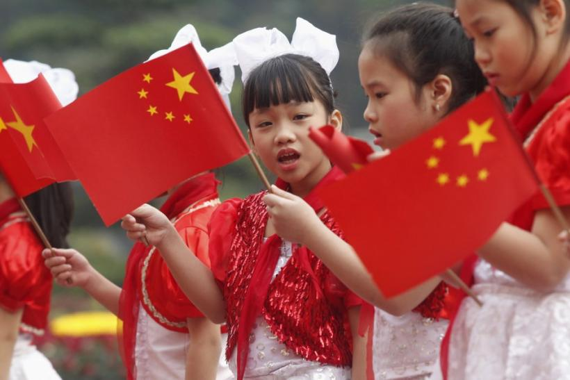 Vietnamese children wave Vietnamese and Chinese flags to welcome the visit to Vietnam by China's Vice President Xi Jinping at the Presidential Palace in Hanoi