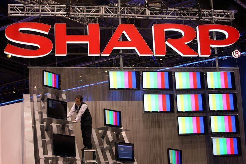A worker prepares a display of Sharp flat panel televisions for the 2009 International Consumer Electronics Show (CES) at the Las Vegas Convention Center in Las Vegas.