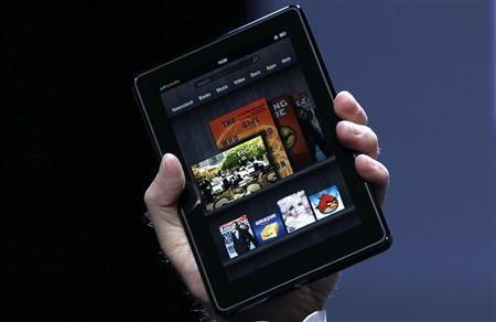 Amazon CEO Jeff Bezos holds up the new Kindle Fire at a news conference during the launch of Amazon's new tablets in New York