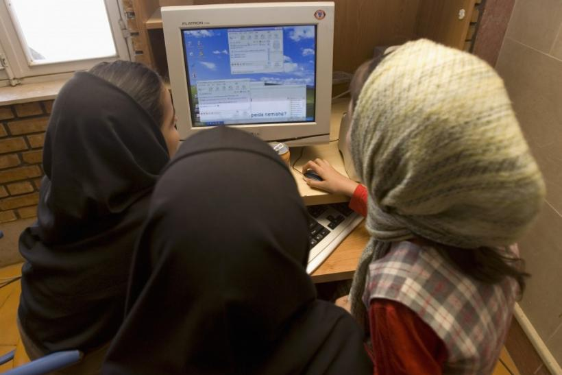 Iranian schoolgirls chat online at an internet cafe