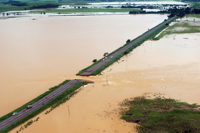 An aerial photograph shows a break in highway BR 356 that was washed away in Campos