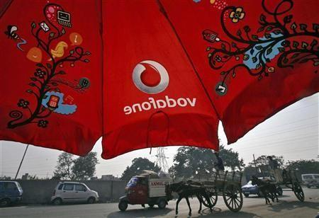 Men ride their horse carts past an umbrella with a Vodafone logo on a road in Jammu November 21, 2011.