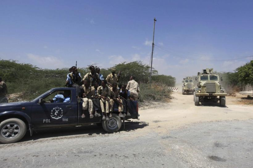 Somalia government soldiers and Ugandan peacekeepers from AMISOM patrol a road following an encounter with Islamist militia in Mogadishu