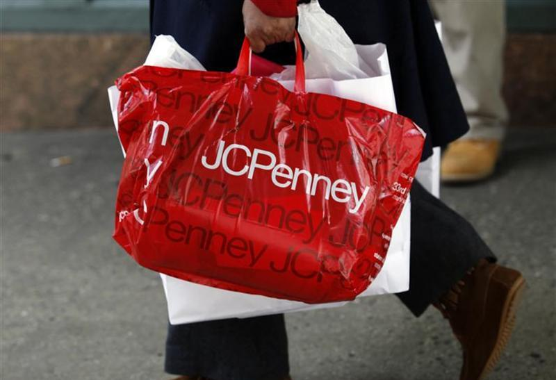 A pedestrian walks with a shopping bag from a JC Penney department store in New York