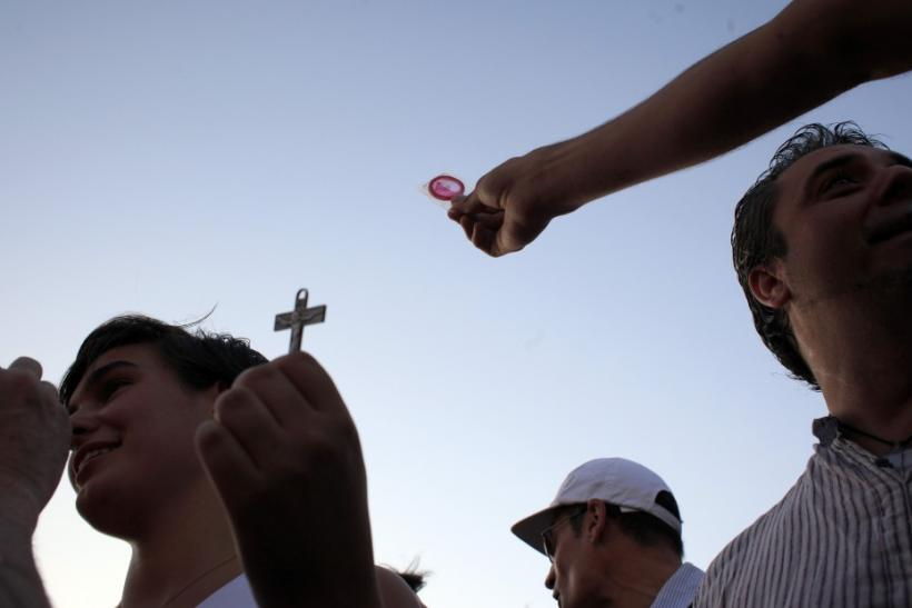 A protester shows a pilgrim a condom who in turn shows him a cross during a demonstration against what they claim is the expensive cost of the papal visit in central Madrid coinciding with the second day of the World Youth Day meeting