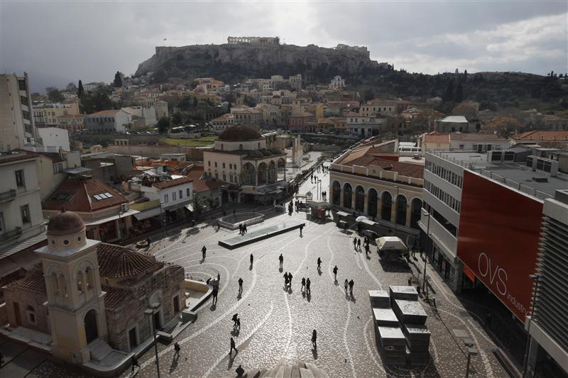 People walk on the Monastiraki square as the Acropolis hill is seen in the background in central Athens