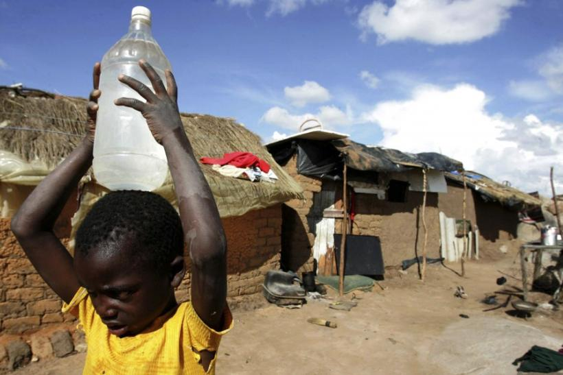 A boy carries a container of water in the suburb of Epworth in Zimbabwe's capital Harare