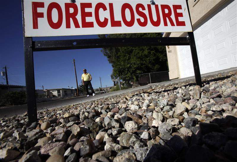 Realtor Mac McCollum stands in front of a foreclosed home in Bullhead City, Arizona
