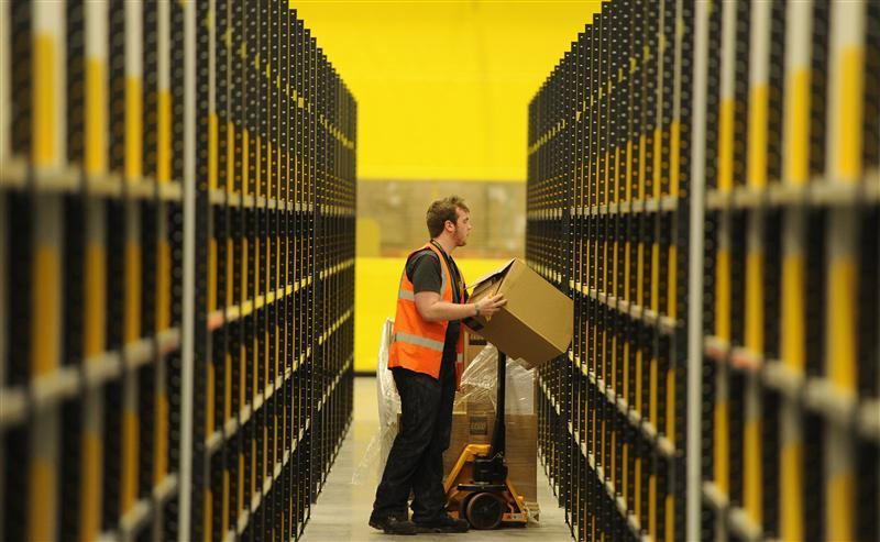A worker lifts a box at Amazon's new fulfilment centre after it