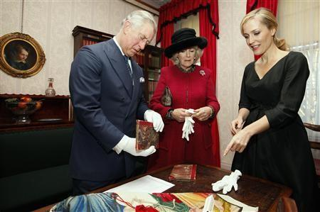 Britain's Prince Charles and his wife Camilla, Duchess of Cornwall, look at two first editions of a Charles Dickens book, as they stand with actress Gillian Anderson during a tour of the Dickens Museum in London