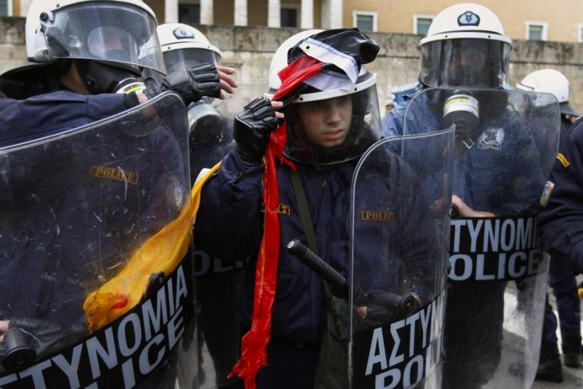 A riot policeman removes a torn German flag thrown by anti-austerity protesters during scuffles in front of the parliament in Athens