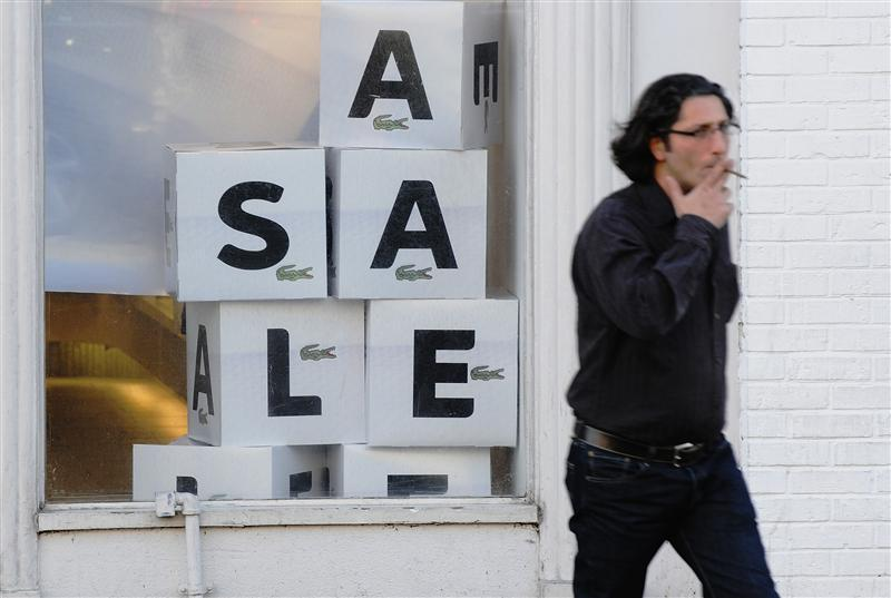 "A man walks past a ""sale"" sign in"