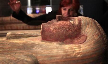 World cultures keeper Henrietta Lidchi poses for a photograph looking at a coffin of Ankhhor during a media viewing of the 'Fascinating Mummies' exhibition at the National Museum of Scotland in Edinburgh, Scotland February 10, 2012.