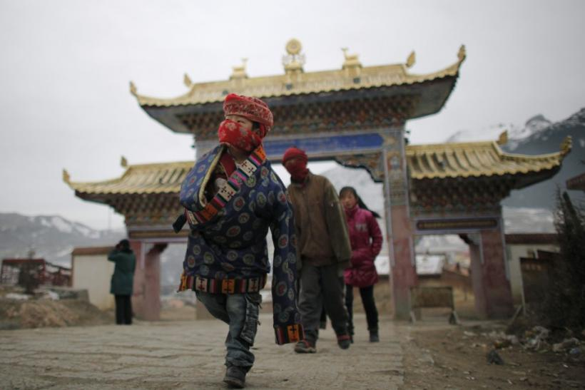 An ethnic Tibetan family arrive at a temple during Tibetan New Year celebrations in Langmusixiang