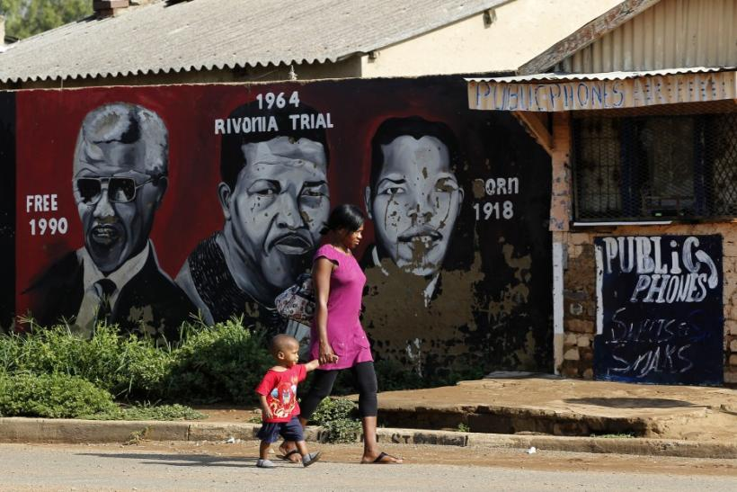 A women and her child walk past portraits of former South African President Nelson Mandela, painted by O.J. Zwane, in Soweto February 26, 2012.