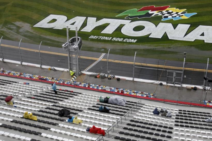 Fans sit in the rain during the delayed NASCAR Sprint Cup Series 54th Daytona 500 race at the Daytona International Speedway in Daytona Beach