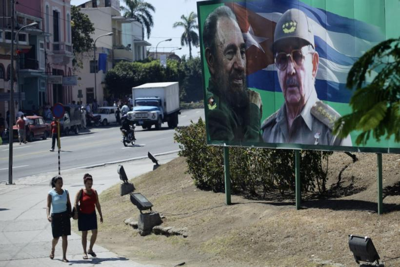People walk beside a billboard with images of former Cuban leader Castro and his brother in Santiago de Cuba