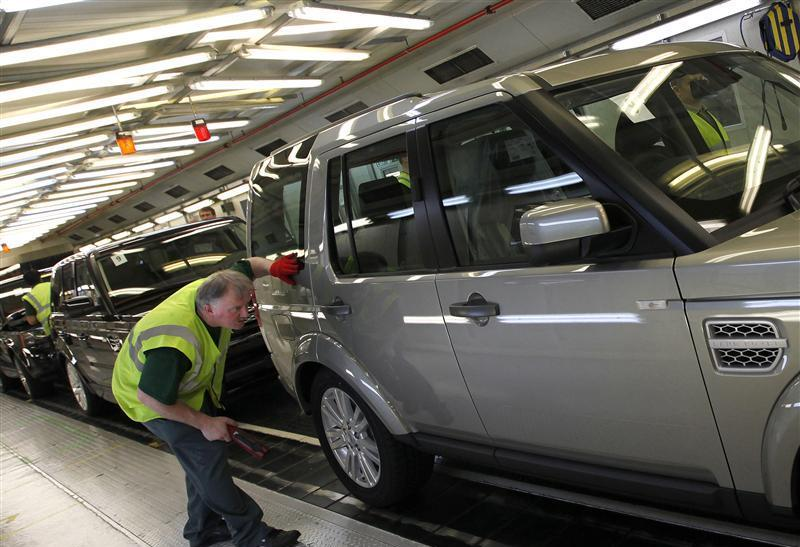 A worker inspects a Land Rover Discovery on the production line at their Production Facility in Solihull