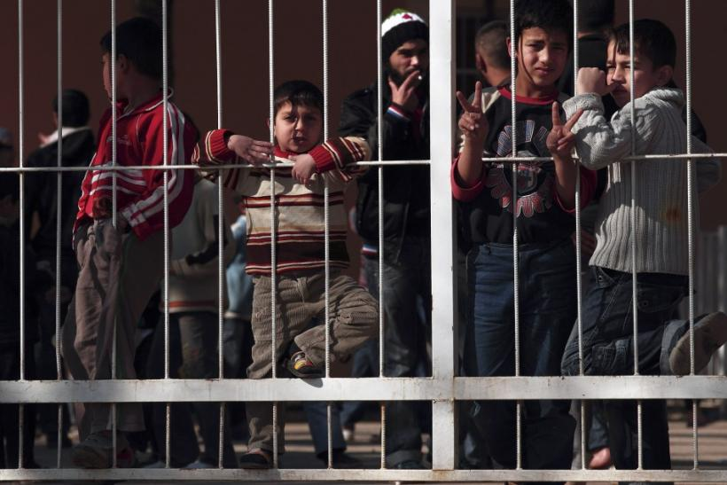 Syrians who fled Syria stand behind the gate of a refugee camp near the Turkish-Syrian border in Yayladagi