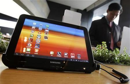 A visitor looks around behind Samsung Electronics' Galaxy Tab 10.1 tablet displayed for customers at a registration desk at South Korean mobile carrier KT's headquarters in Seoul December 9, 2011.