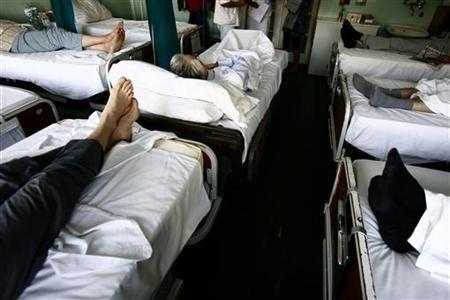 People are seen on beds in a room at the National Cancer Research Center within the Institute for Oncology and Radiology in Belgrade, October 6, 2009.