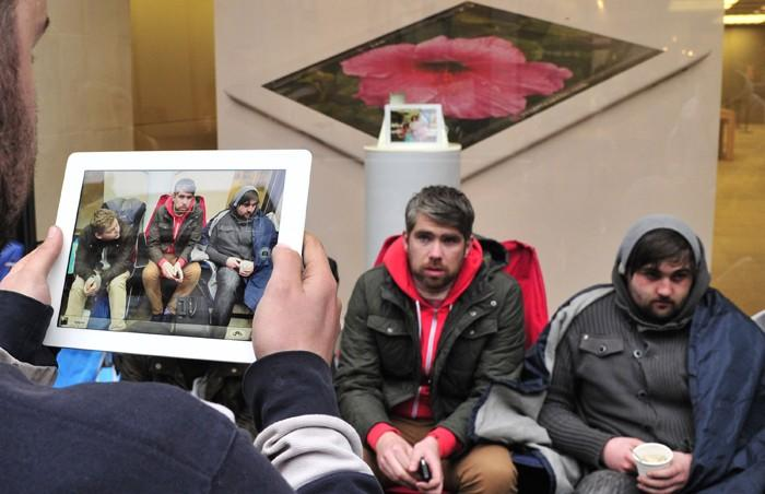 A man uses his iPad to photograph customers who have slept outside a store for 48 hours waiting to purchase new Apple iPad tablet computers in central London
