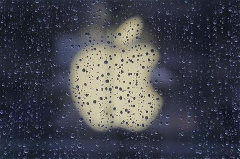Raindrops are seen in front of an Apple logo outside an Apple store in Shanghai February 22, 2012.