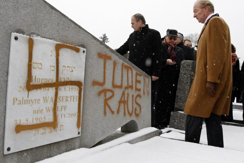 """France's Interior Minister Hortefeux walks next to a tombstone desecrated by vandals with Nazi swastikas and the Slogan """"Jews out"""", in the Jewish Cemetery of Cronenbourg"""