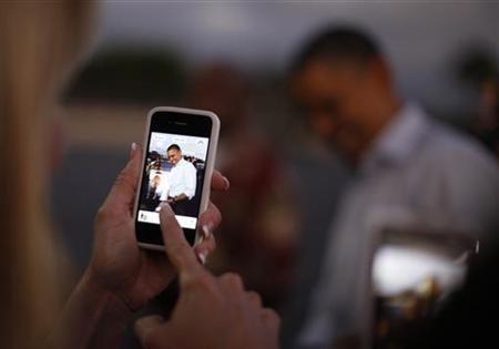 A woman takes a picture of U.S. President Barack Obama with her iPhone upon his arrival at Hickam Air Base near Honolulu, Hawaii, December 23, 2011.