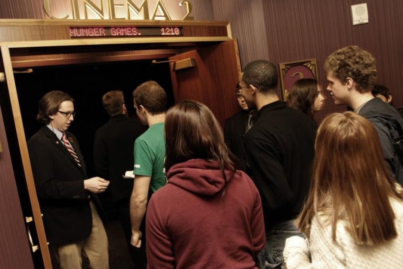"Movie attendees enter a theater on the opening night of ""The Hunger Games"" at Regal Cinemas in Los Angeles, California March 22, 2012."