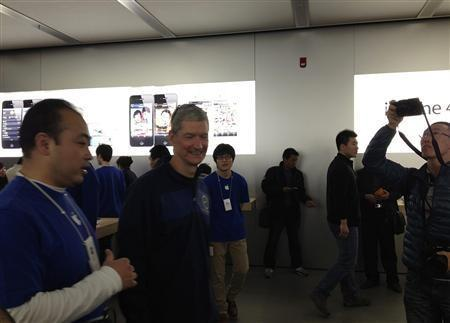 Apple CEO Tim Cook (2nd L) talks to employees at an Apple store in central Beijing, March 26, 2012.