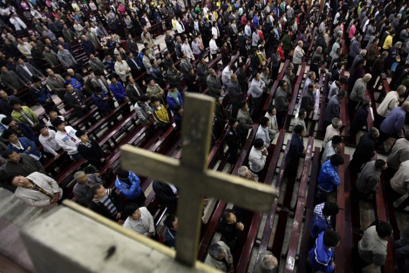 Worshippers pray during a mass at the Liuhe Catholic Church on the outskirts of Qingxu county