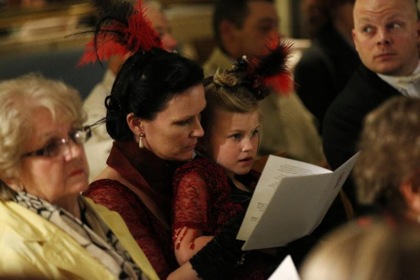 Passengers sing hymns during a religious service of remembrance aboard the Titanic Memorial Cruise in the western Atlantic Ocean