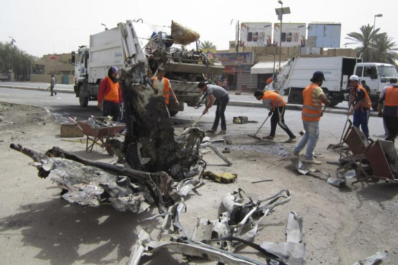 Municipality workers clean the site of a bomb attack on Palestine street in eastern Baghdad