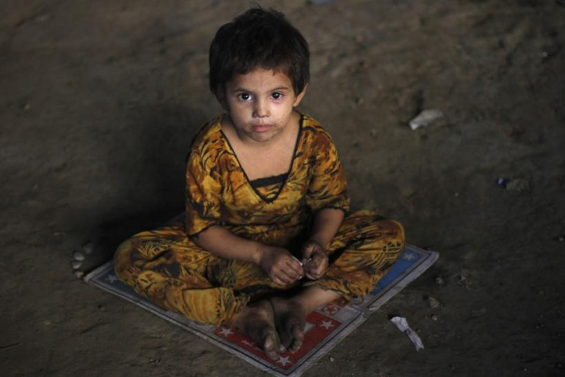 A three-year-old homeless Hindu girl, is photographed as she sits on a board game while taking shelter under a b