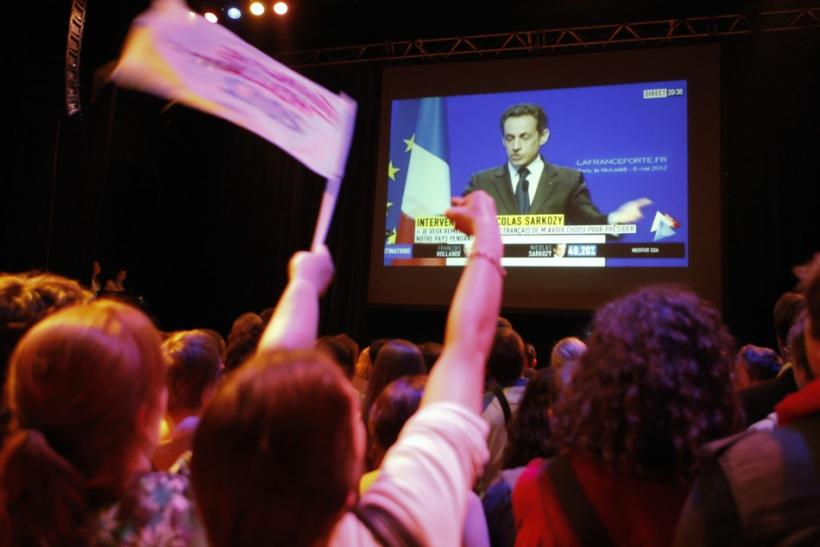 Supporters of newly-elected French President Francois Hollande watch as outgoing French President Nicolas Sarkozy appears on a television screen to announce his defeat in the 2012 French presidential elections in a concert hall in Villeurbanne May 6, 2012