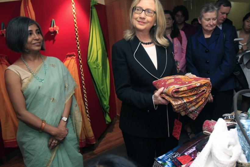 U.S. Secretary of State Hillary Clinton (2nd L) holds a sari during an anti-human trafficking event in Kolkata May 6, 2012.