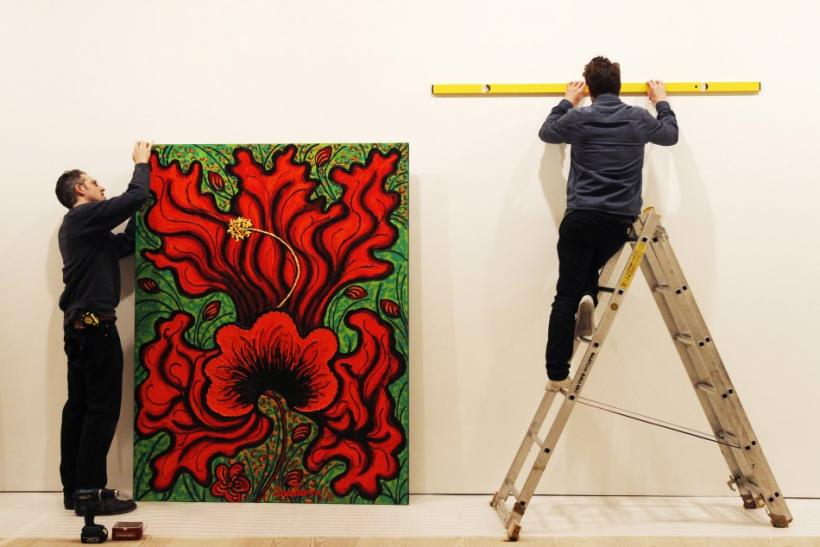 "Technicians hang artist Ana Tzarev's painting ""Love (Hibiscus)(Garden La Fleur du Cap)"" at the Saatchi Gallery in London May 17, 2012. Thione hopes his Artify It service will mark a major departure from the traditional gallery setting"