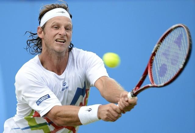 David Nalbandian of Argentina hits a return to Grigor Dimitrov of Bulgaria during their men's singles tennis match at the Queen's Club tournament in London