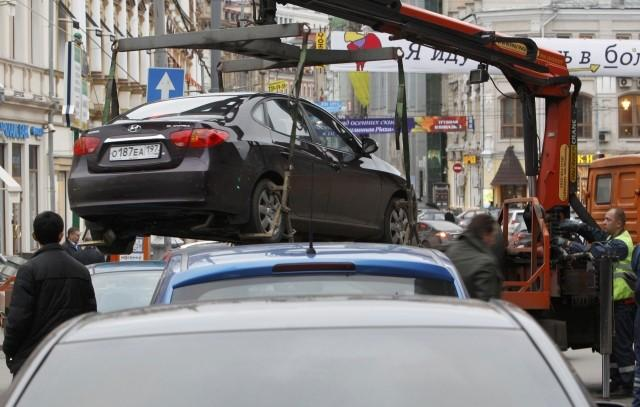 File photo of city authorities lifting a car parked on a pedestrian crossing before towing it away in Moscow. This is w