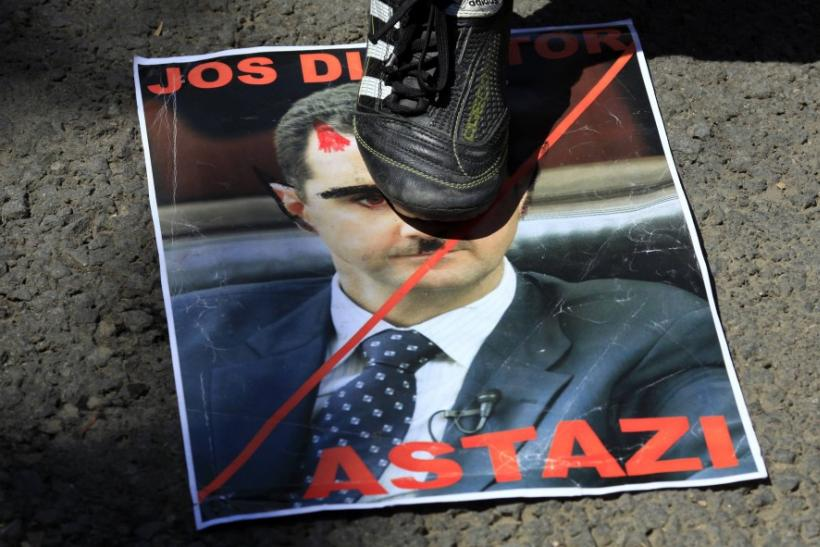 http://s1.ibtimes.com/sites/www.ibtimes.com/files/styles/v2_article_large/public/2012/07/19/289319-assad-poster-protest.jpg