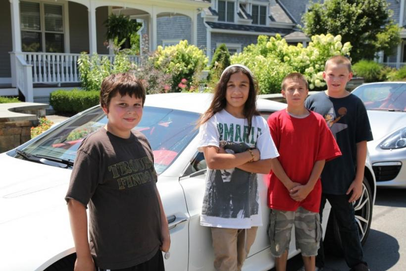 Four neighborhood children stand for a picture in front of the cars in Saratoga Springs.
