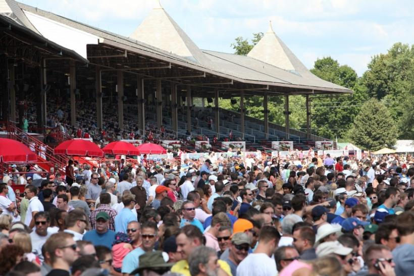 The crowd gathered by the track for the races at the Saratoga Race Course on opening weekend.